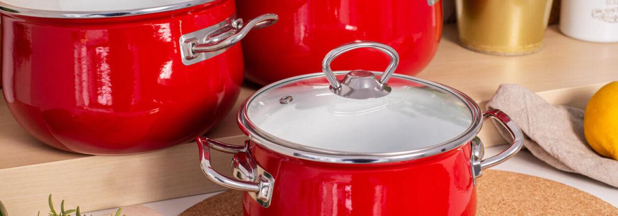 czerwone garnki emaliowane na kuchennym blacie