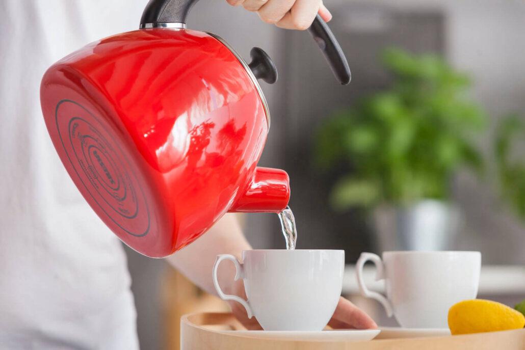 kobieta nalewa wodę do kubka z czerwonego czajnika emaliowanego